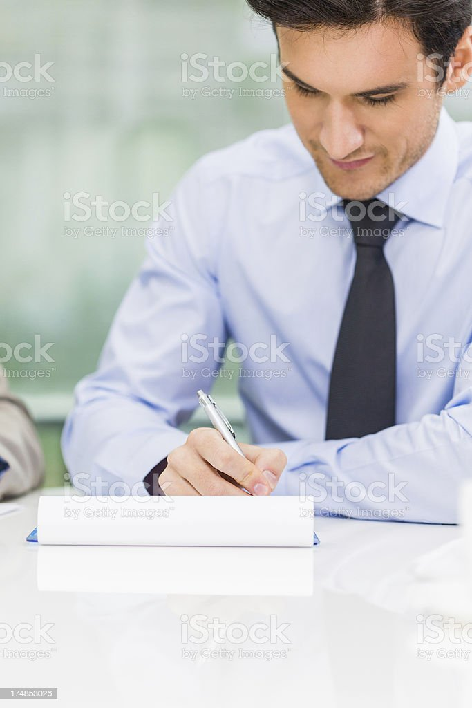 Young businessman taking notes on a meeting royalty-free stock photo