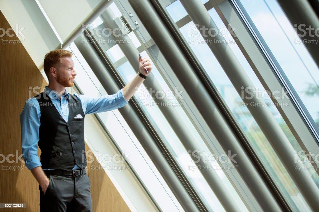 Joven empresario tomando selfie cerca de la ventana - foto de stock