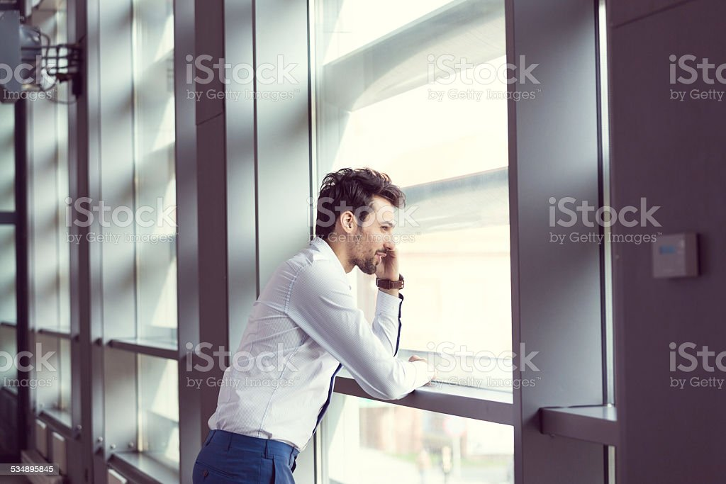 Young businessman talking on cell phone Young businessman wearing white shirt standing by the window in an office and talking on smart phone. 2015 Stock Photo