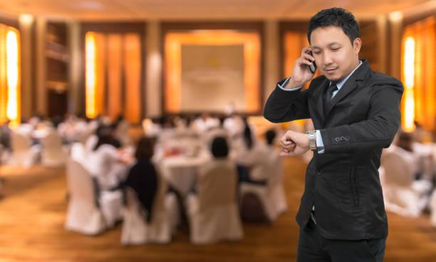 jonge zakenman praten op mobiele telefoon en horloge op abstracte wazig foto van hall of seminar conferentieruimte met genodigden achtergrond, bedrijfsconcept - call center stockfoto's en -beelden