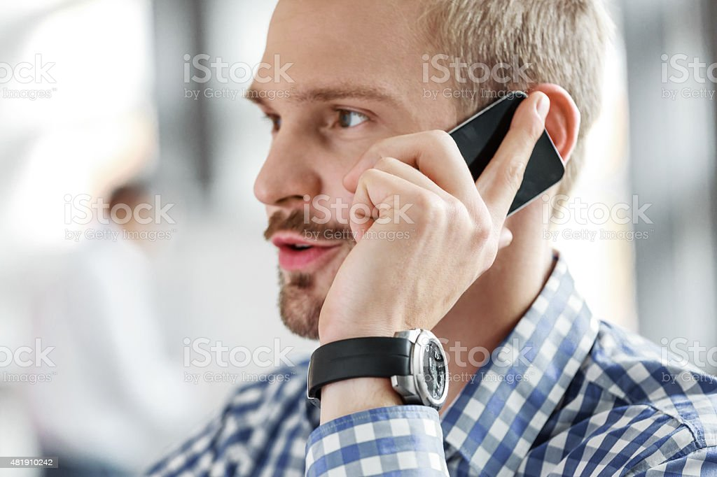 Young businessman talking on mobile phone Portrait of friendly young businessman wearing checkered shirt talking on smart phone. Close up of face and hand. 2015 Stock Photo