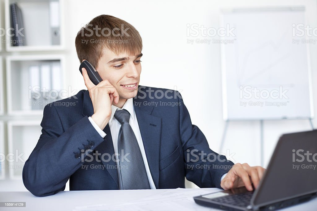 young businessman talking on phone and working in office royalty-free stock photo