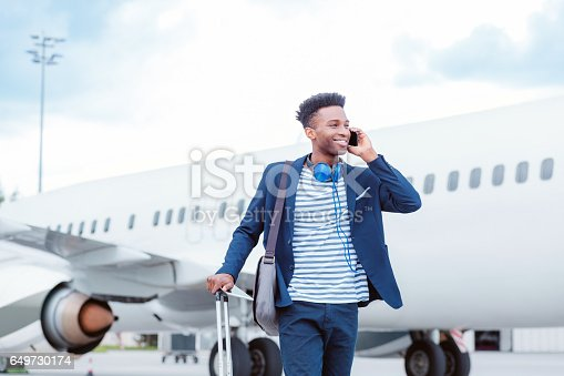 istock Young businessman talking on smart phone in front of airplane 649730174