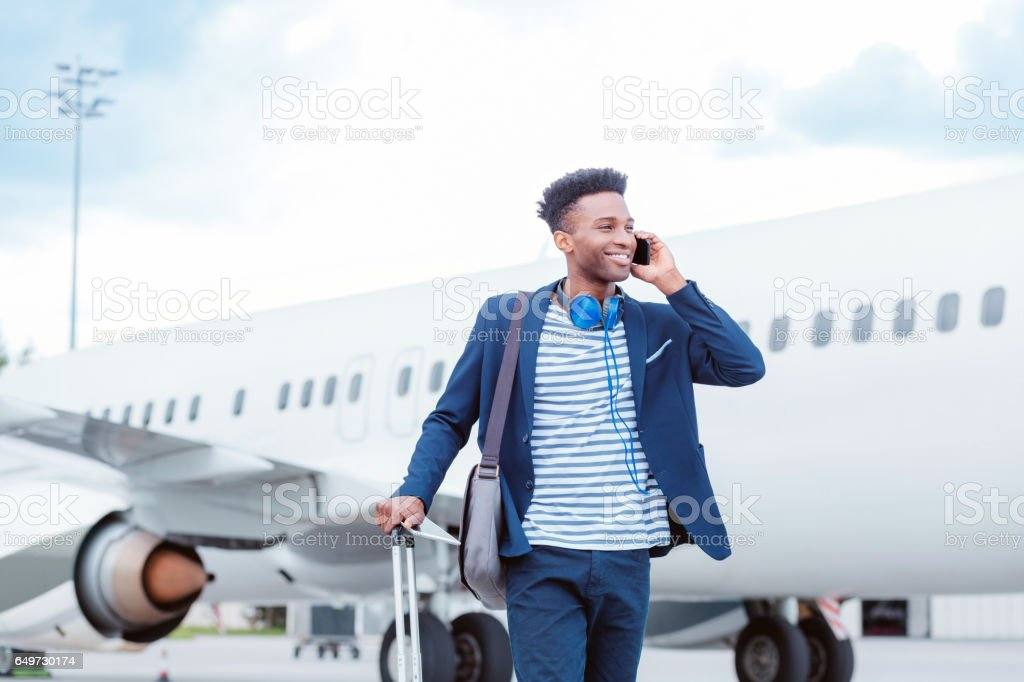 Young businessman talking on smart phone in front of airplane stock photo