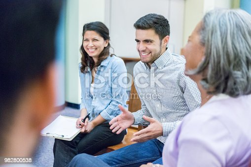 956725740istockphoto Young businessman talks with colleagues 982800538