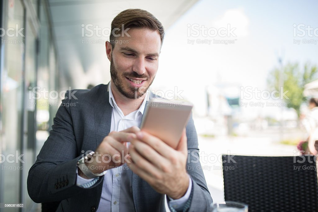 Young businessman text messaging during coffee break outdoors. royalty-free stock photo