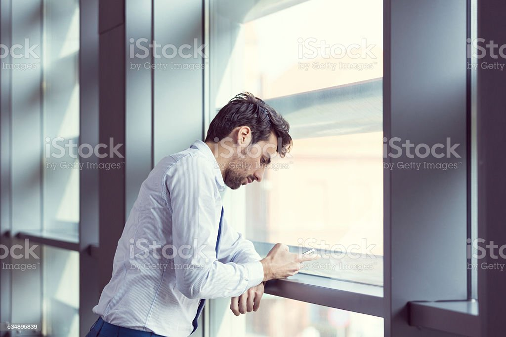 Young businessman texting on smart phone Young businessman wearing white shirt standing by the window in an office and texting on smart phone. 2015 Stock Photo