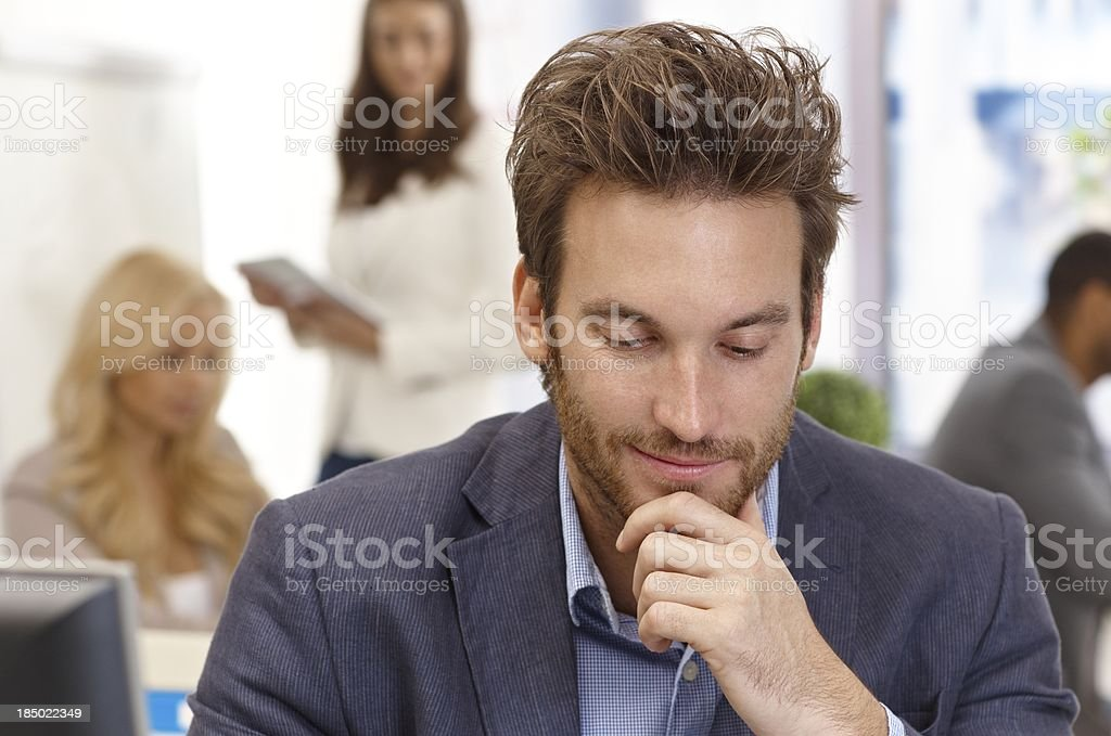 Young businessman thinking in office royalty-free stock photo