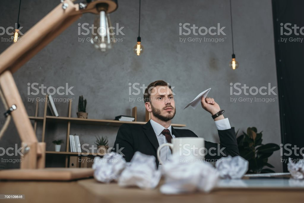 young businessman throwing paper airplane while sitting at workplace stock photo