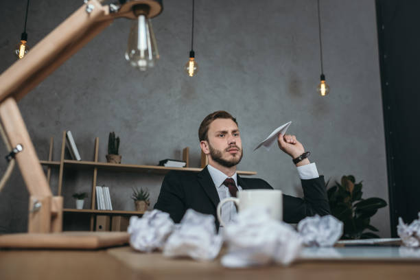 young businessman throwing paper airplane while sitting at workplace - tedious stock photos and pictures