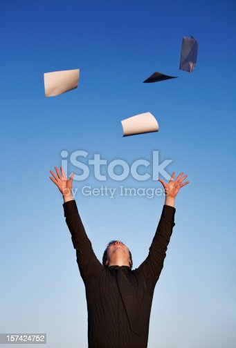 157312920 istock photo Young businessman throwing paper in air, blue sky 157424752