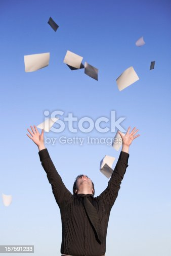 157312920 istock photo Young businessman throwing paper in air, blue sky 157591233