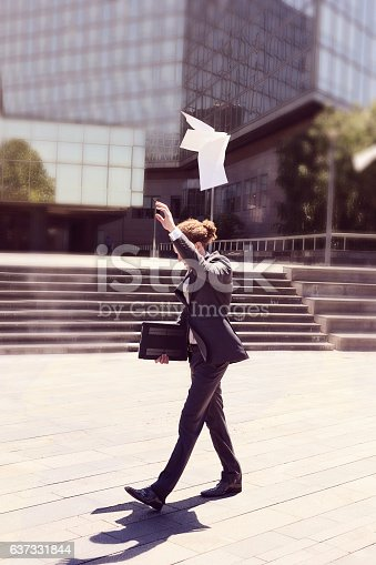 157312920 istock photo Young businessman throwing paper 637331844