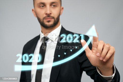 istock Young businessman touching virtual arrow. 1204395963