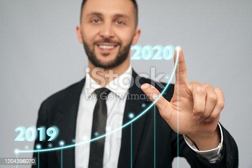istock Young businessman touching virtual arrow. 1204396070