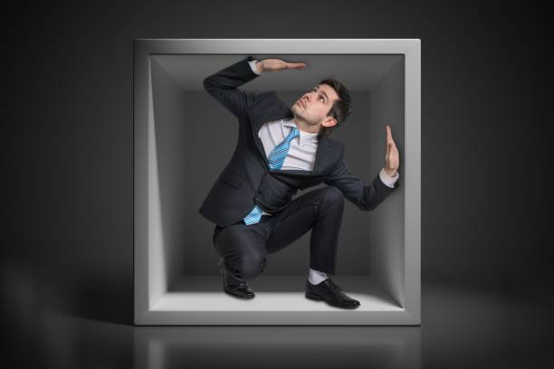 Young businessman trapped inside uncomfortable small box. Young businessman trapped inside uncomfortable small box. trap stock pictures, royalty-free photos & images