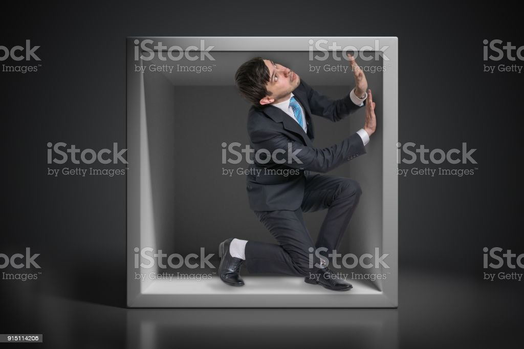 Young businessman trapped inside uncomfortable small box. stock photo