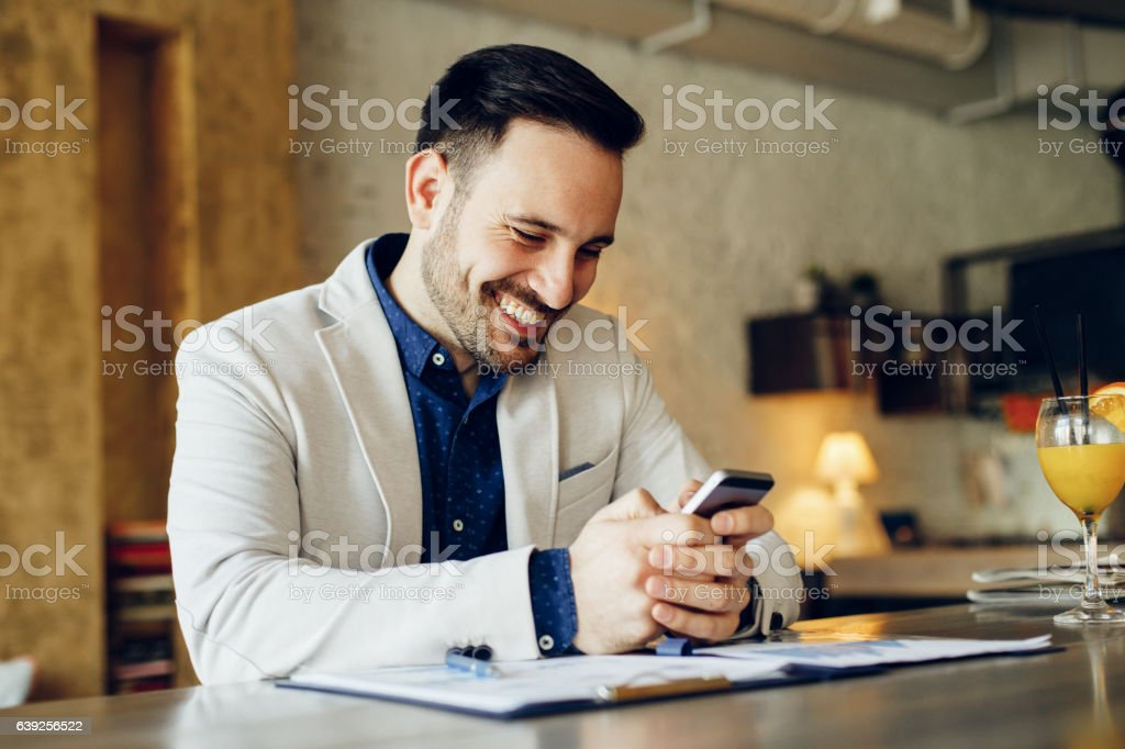 Young businessman typing message on phone in cafe – Foto