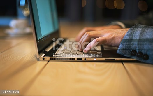 Young businessman typing on a laptop.