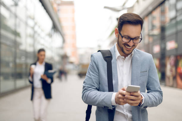 Young businessman typing text message on his way to work stock photo