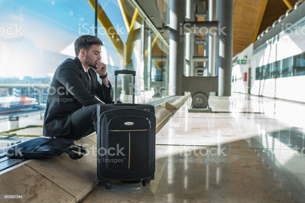 young businessman upset at the airport waiting his delayed flight with luggage stock photo