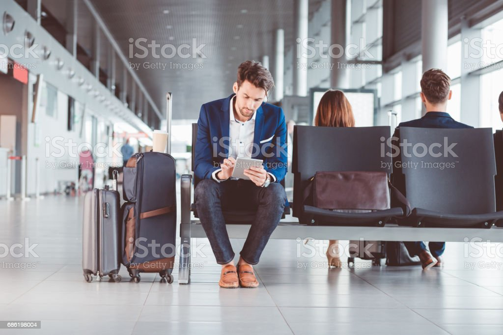 Young businessman using a digital tablet in airport waiting area stock photo