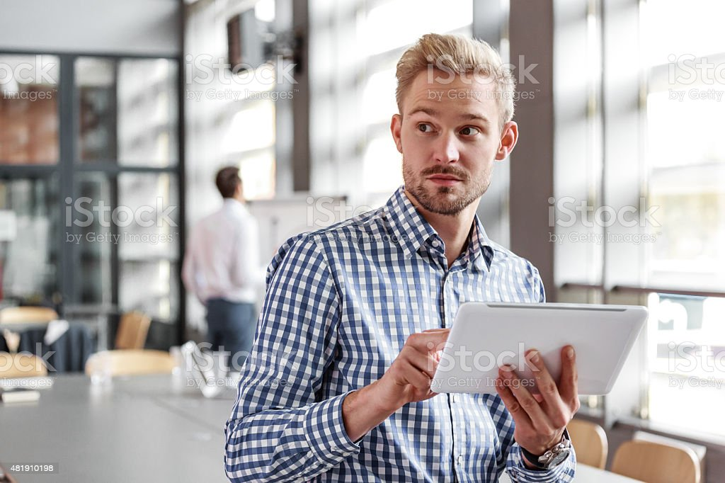 Young businessman using a digital tablet in the office Portrait of young blond hair bearded businessman wearing checkered shirt sitting in the board room, holding a digital tablet in hand and looking away. Coworker in the background. 2015 Stock Photo