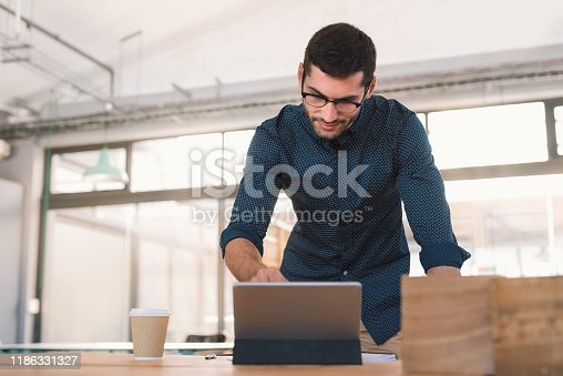 Focused young businessman leaning over his office desk working online with a digital tablet