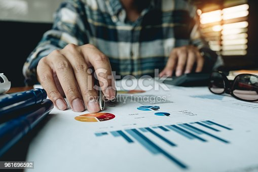 istock Young businessman using calculator for analysis financial document with chart graph at home office 961696592