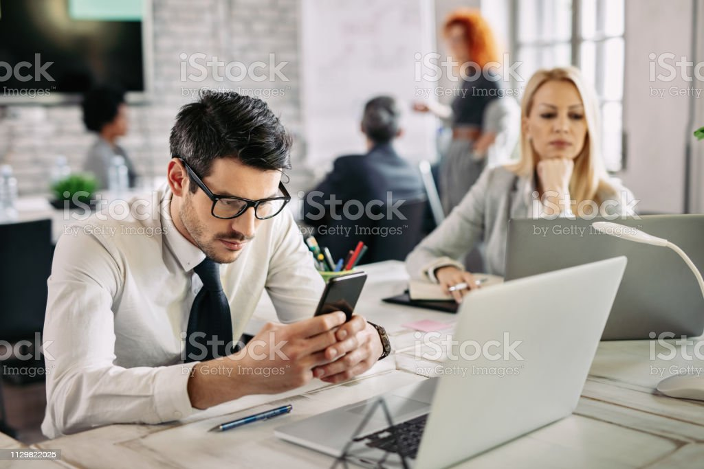 Young businessman using cell phone while working in the office. - Royalty-free Adult Stock Photo