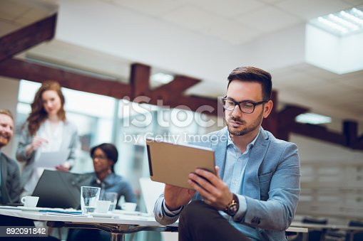 istock Young businessman using digital tablet and analyzing business report. 892091842