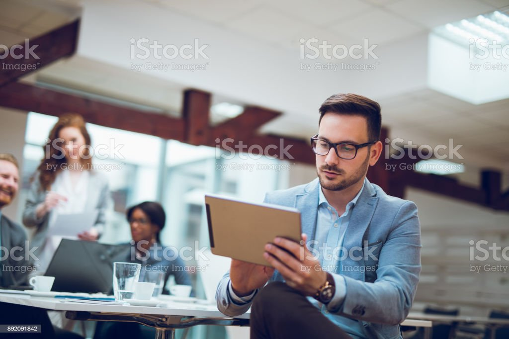 Young businessman using digital tablet and analyzing business report. stock photo