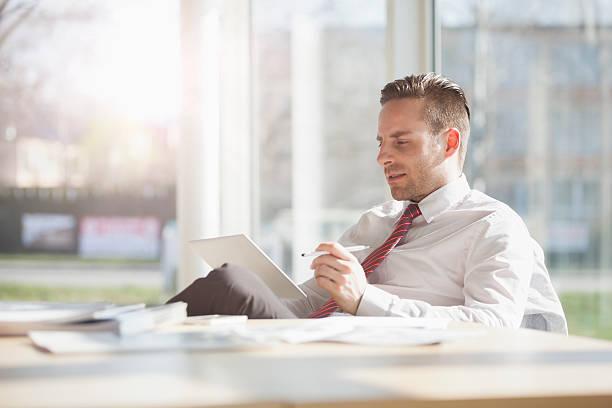 Junge Geschäftsmann mit Digitaltablett am Schreibtisch in kreative Büro – Foto