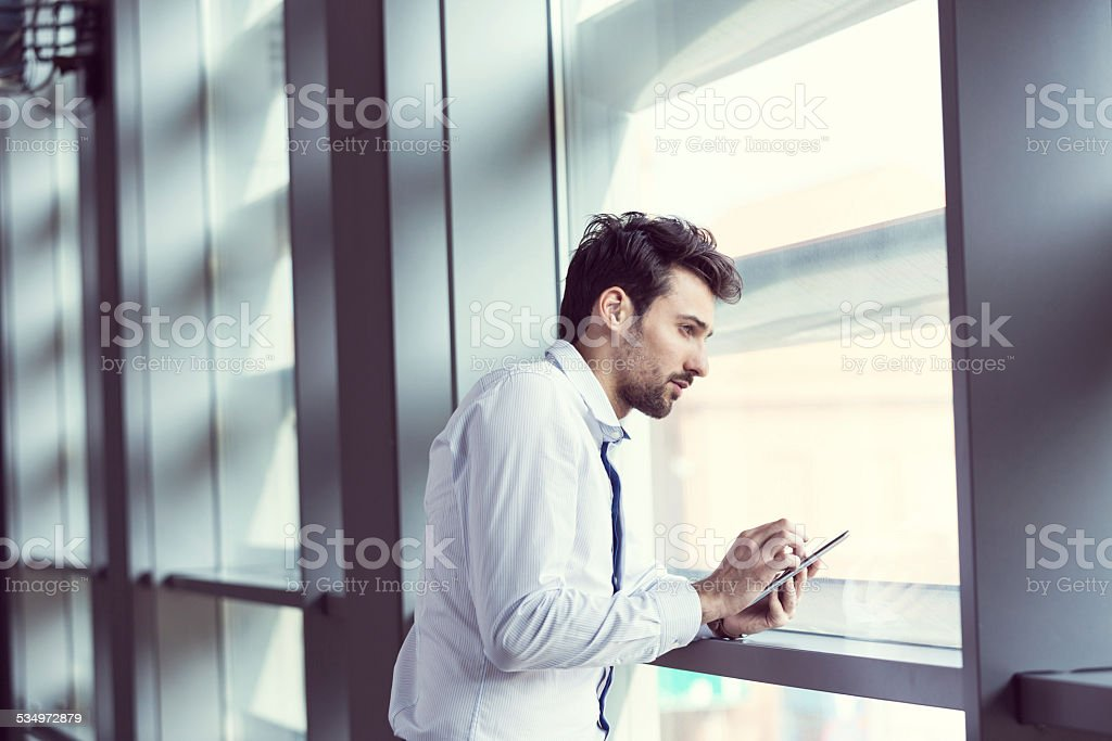 Young businessman using digital tablet by the window Young businessman wearing white shirt standing by the window in an office and using a digital tablet. 2015 Stock Photo