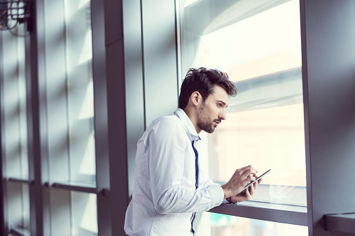 Young Businessman Using Digital Tablet By The Window Stock Photo - Download Image Now