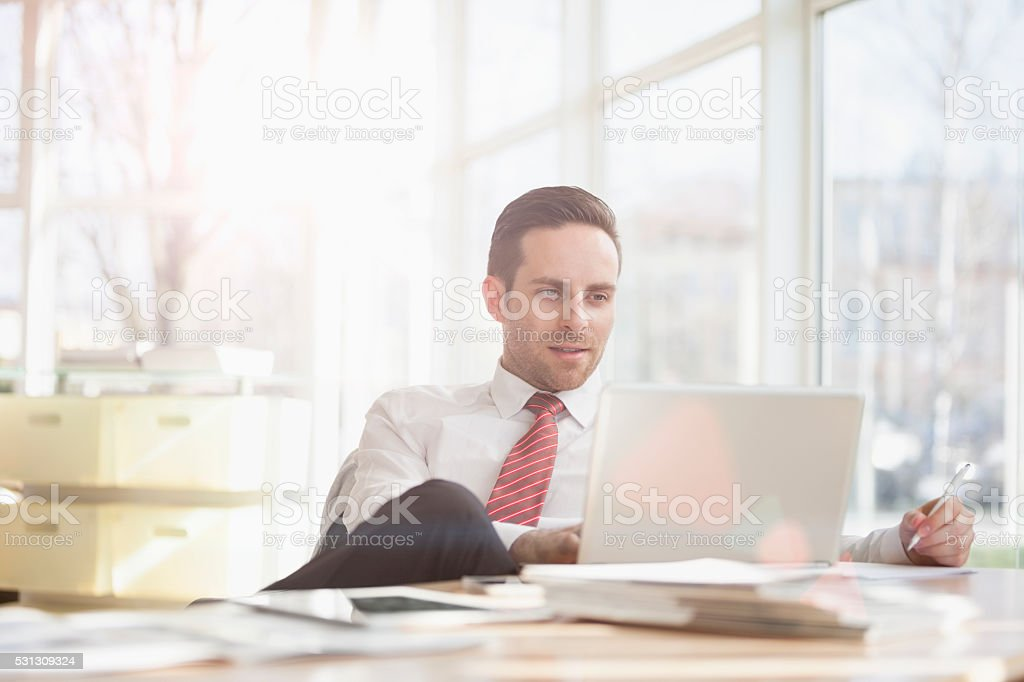 Young businessman using laptop at office desk stock photo