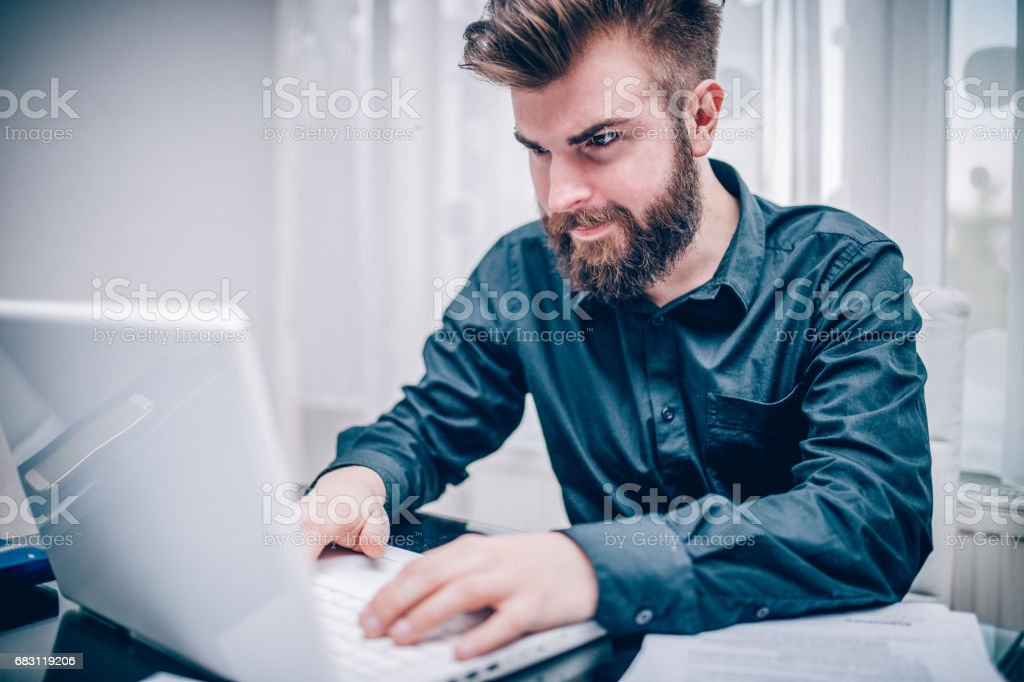 Young businessman using laptop in the office stock photo
