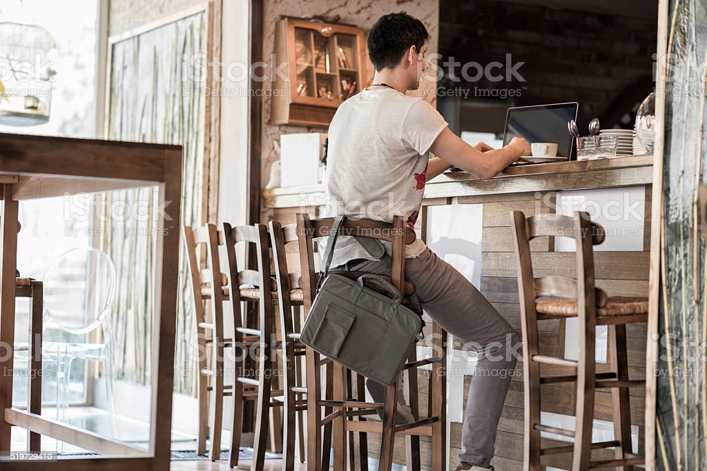 Young Businessman Using Laptop on a Break in a Cafe stock photo