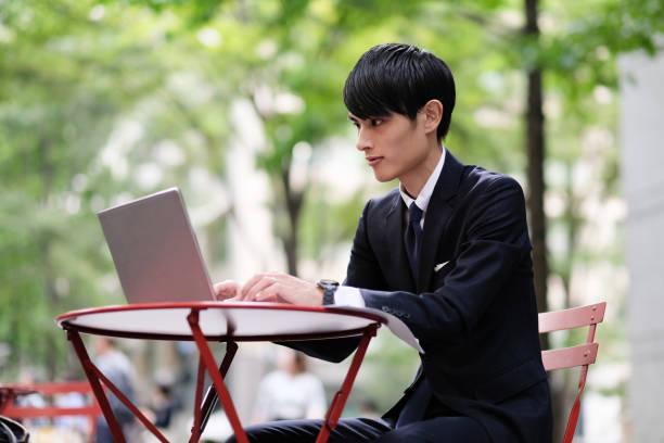 路上でラップトップを使用して若いビジネスマン - 椅子 家具 ストックフォトと画像