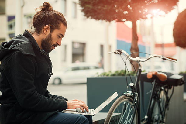 Young Businessman Using Laptop Outdoors. Young businessman riding bicycle to and from his office. Making break, sitting on the bench and using his laptop. His bicycle is beside him. man bun stock pictures, royalty-free photos & images