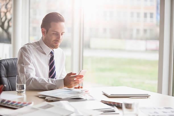 Junge Geschäftsmann mit Mobiltelefon im Büro-Schreibtisch – Foto