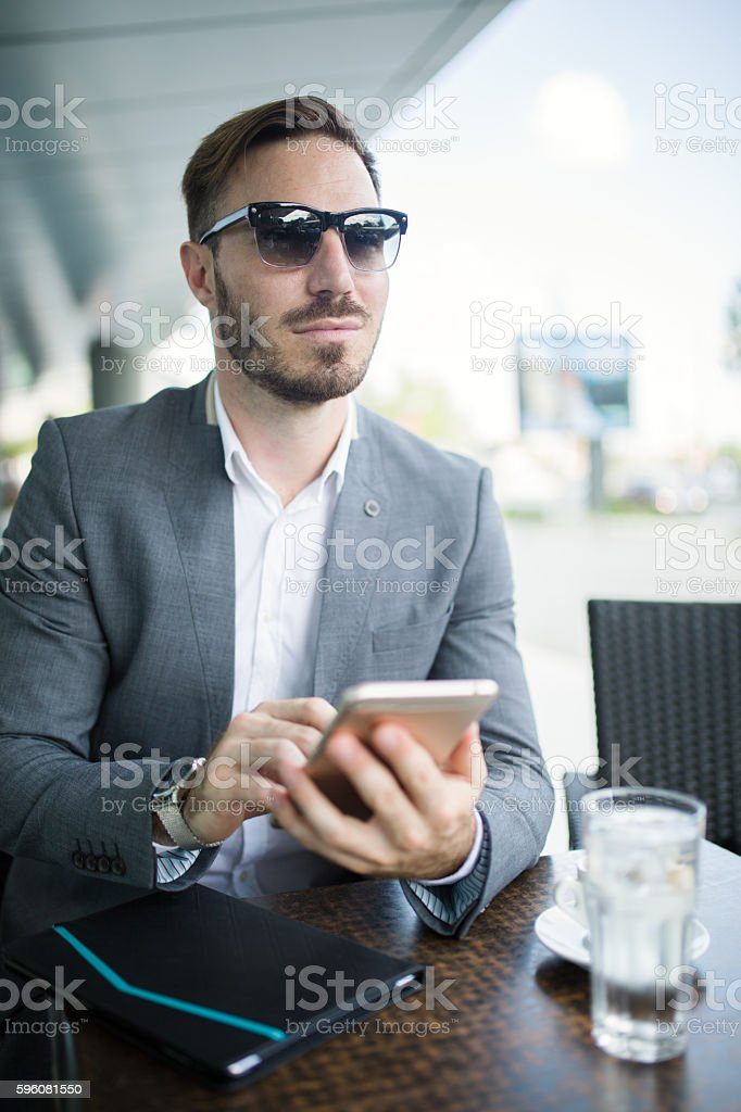Young businessman using mobile phone during coffee break outdoors. royalty-free stock photo