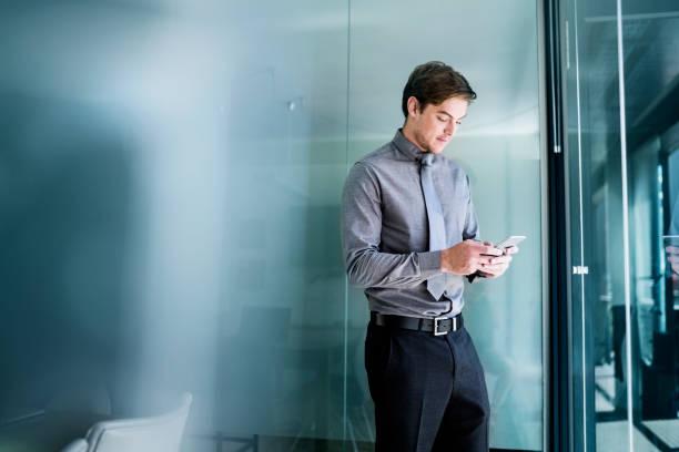 オフィスで携帯電話を使用している若いビジネスマン ストックフォト