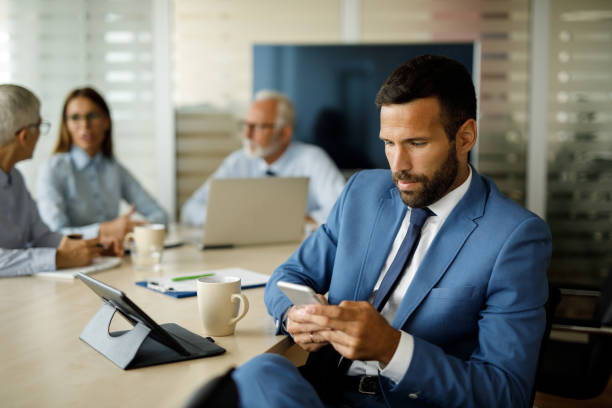 Young businessman using mobile phone in the office stock photo