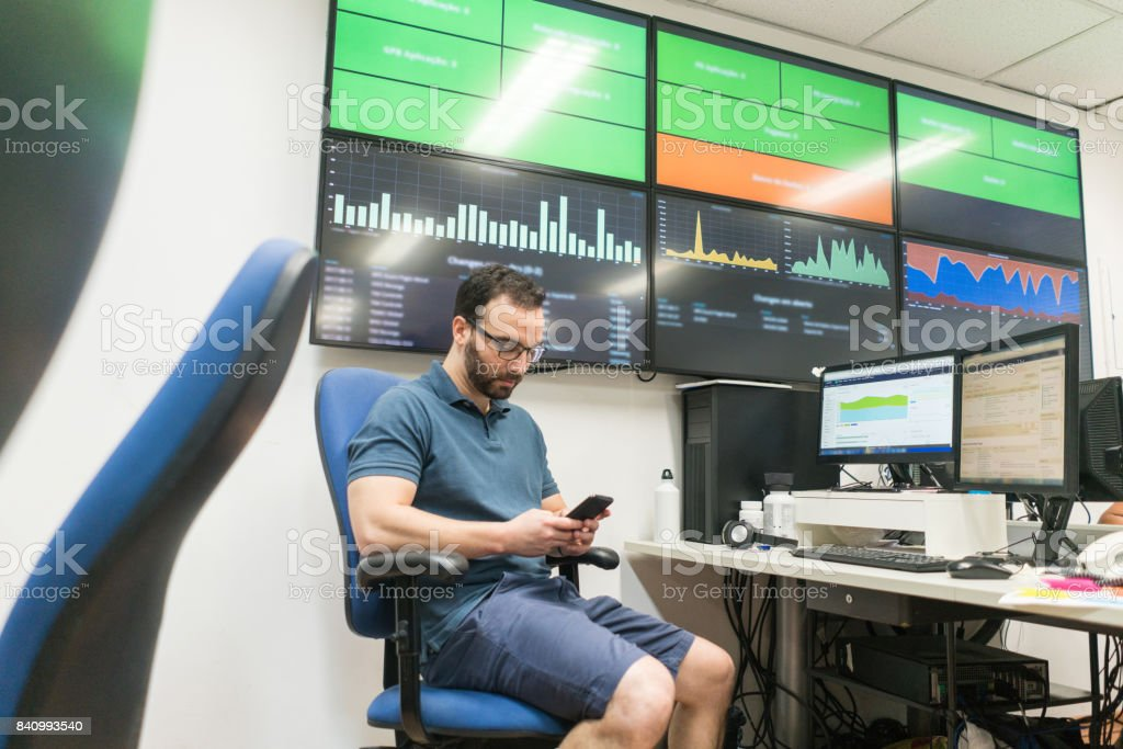 Young businessman using mobile phone while sitting by big screen television in creative office stock photo