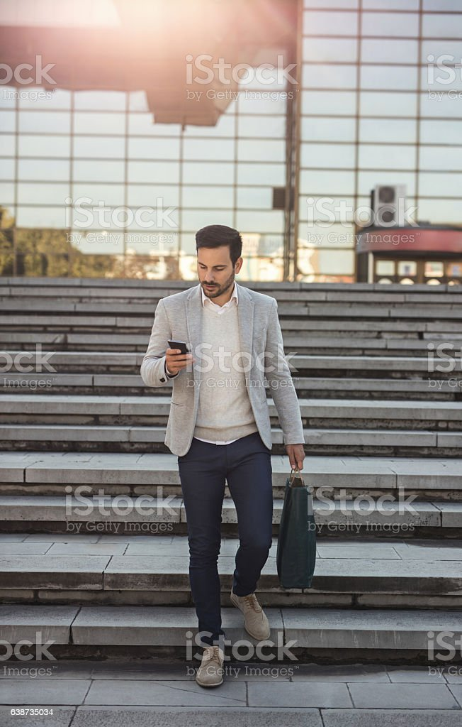 Young businessman using mobile phone while walking downstairs. stock photo