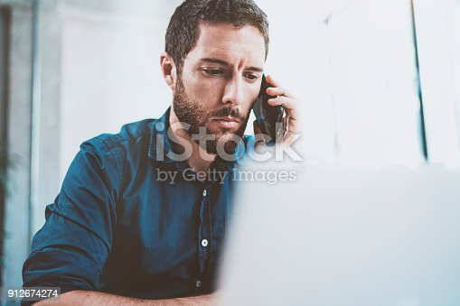 istock Young businessman using smartphone at office and making notes.Blurred background.Horizontal.Cropped. 912674274