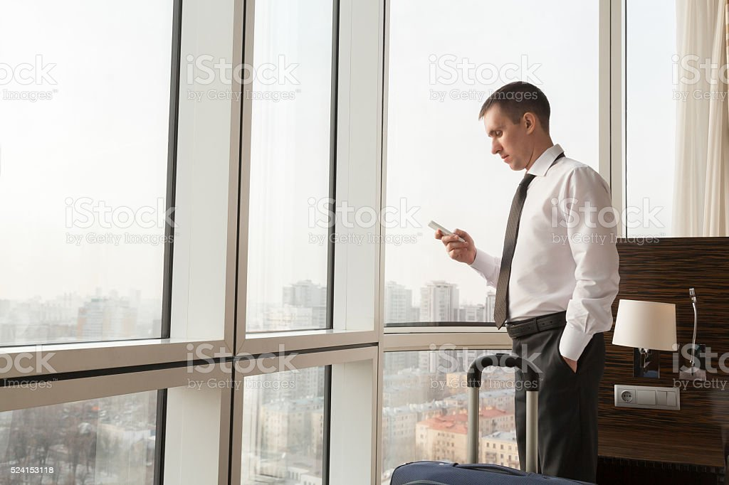 Young businessman using smartphone in hotel room stock photo