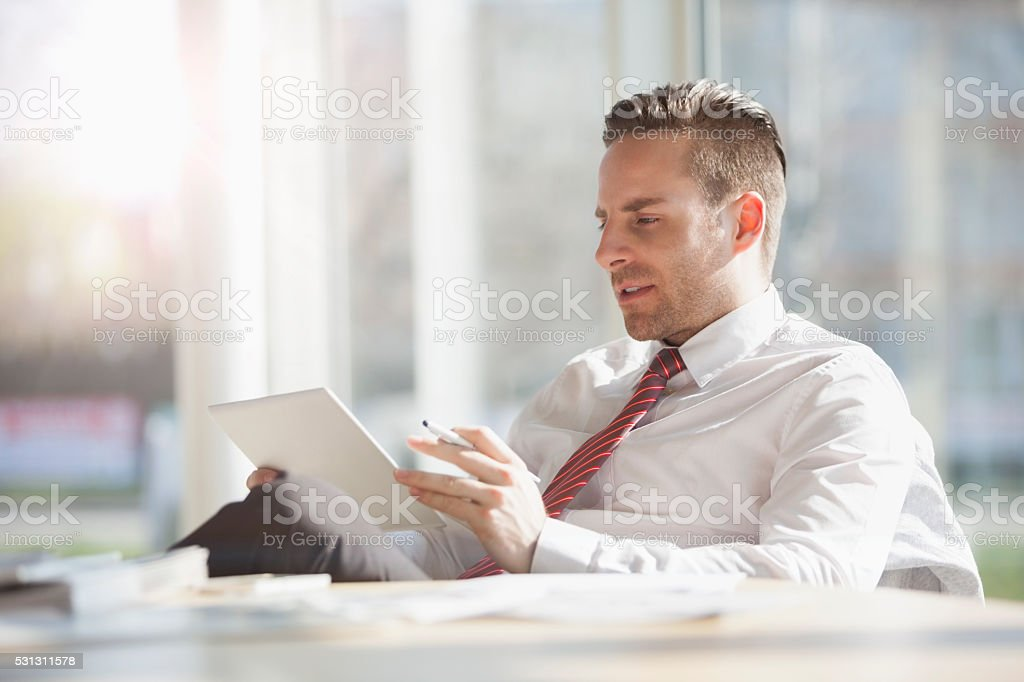 Young businessman using tablet at desk in creative office stock photo