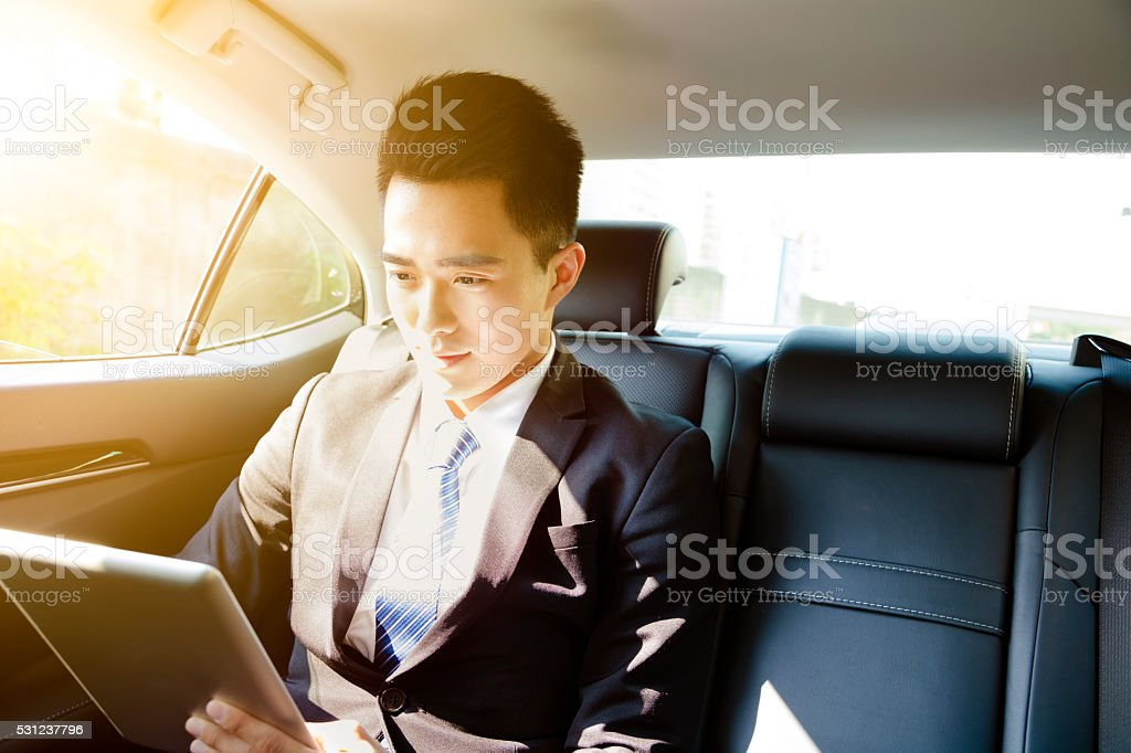 young businessman using tablet pc in car at morning圖像檔